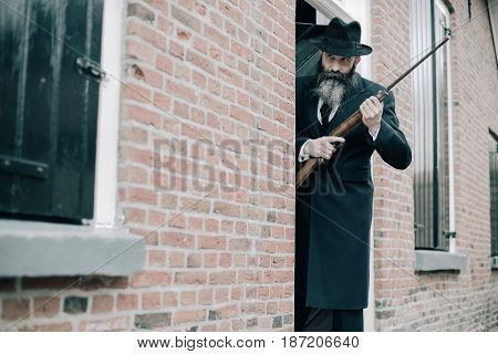Man With Long Beard Dark Dressed Standing With Rifle Ready To Shoot.