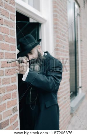 Long Bearded Man Shooting With Rifle Along Wall Near Front Door.