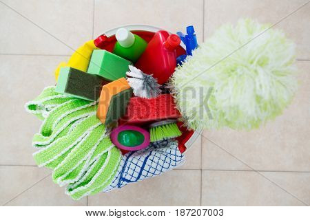 Overhead view of various cleaning products in bucket on tiled floor
