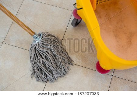 Overhead view of mop by bucket on tiled floor