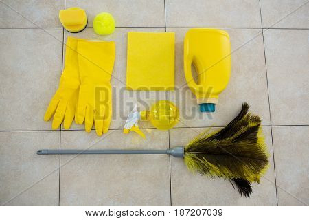 Overhead view of cleaning products and duster on tiled floor