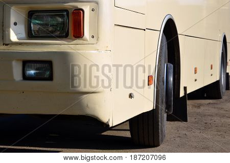 Photo Of The Hull Of A Large And Long Yellow Bus. Close-up Front View Of A Passenger Vehicle For Tra