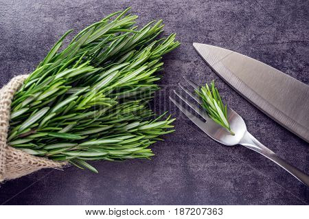 Bouquet of fresh rosemary in burlap bag tied with twine. The knife and fork. Spices.