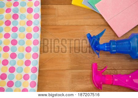 High angle view of spray bottle with wipe pad on wooden table