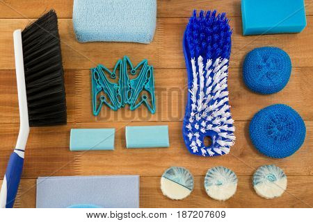 Overhead view of brushes and sponge with soaps on wooden table