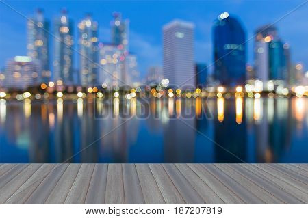 Opening wooden floor Twilight blurred bokeh light Office buildig with water reflection abstract background