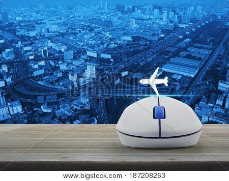 Airplane icon with wireless computer mouse on wooden table over city tower street and expressway Business transportation concept