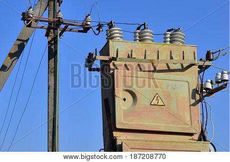 Old And Obsolete Electrical Transformer Against The Background Of A Cloudless Blue Sky. Device For D