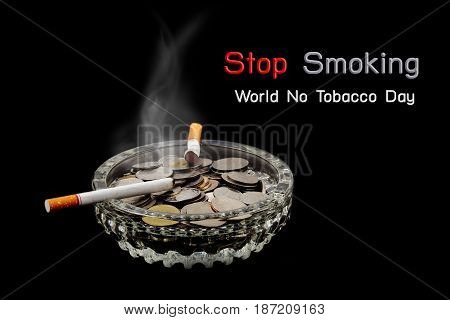 World No Tobacco Day Cigarette is burning with smoke and coins in ashtray on dark background.