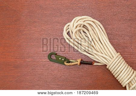 Twisted rope with a carabiner on a wooden background