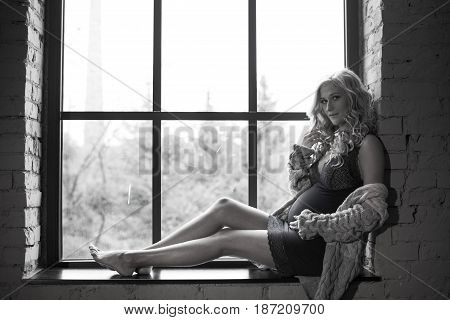 Beautiful red-haired pregnant girl sits on a window with a bouquet of flowers