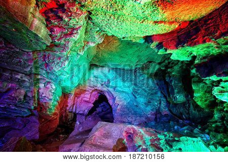Entrance to ice cave. The hole in the cave, painted in fantastic colors