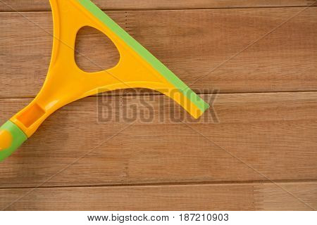 Cropped image of yellow wiper on wooden table
