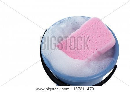 High angle view of sponge in bucket with soap sud against white background