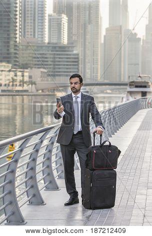 Businessman with a suitcase on a phone in Dubai Marina UAE