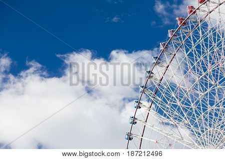 Funfair big ferris wheel against white clouds and blue sky background