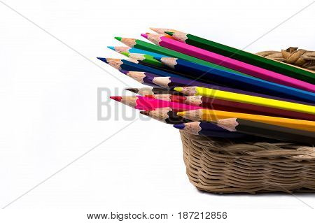 Color pencils in the basket isolate on white background Color pencils, variety of colors are covered with small cylindrical wooden rods. It is a simple material and widely used in creating artwork, especially good for young children and who just started p