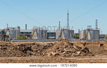 The old tank farm for storage of petroleum products against the background of a mound