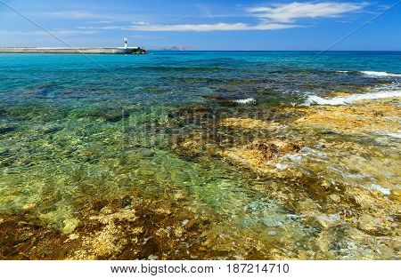 Waves break on rocky shore. Coast and beach resort village. Clear day at sea. Crete island, Greece, Beach Caves