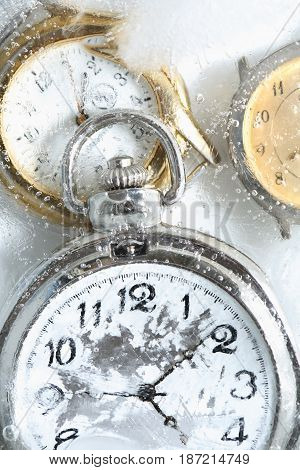 Permafrost concept. Closeup of pocket watch under frozen water surface with ice