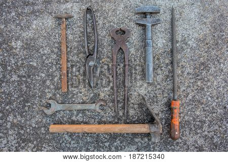 Collection of vintage hand tools laid out on weathered concrete