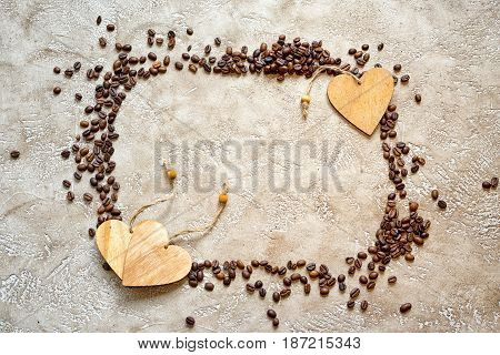 Rectangular silhouette frame made from coffee beans with wooden heart tags and copy space top view.