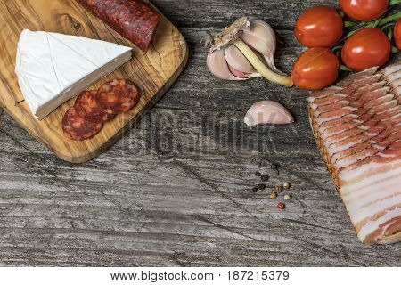 Top view of the old wooden desk with hot sausage Chorizo tomatoes garlic bulb and a piece of the Petite Brie cheese.