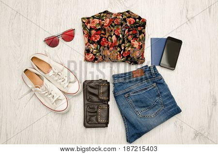 Shirt In Flowers, Glasses, Sneakers, Jeans, Phone And Passport. Wooden Background. Fashionable Conce