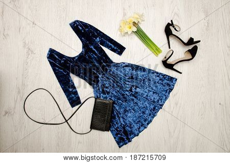 Velvet Blue Dress, Black Shoes, Clutch And A Bouquet Of Daffodils. Fashionable Concept. Wooden Backg