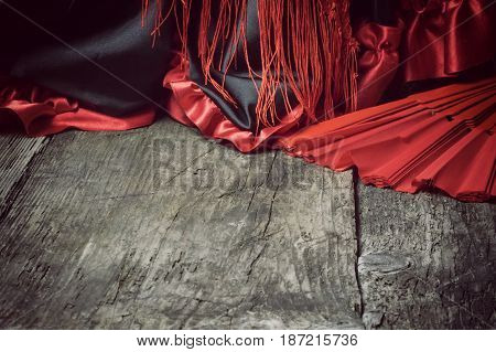 Clothing for Flamenco dance. Clothes red scarf with tassels and red fan are on the old wooden desk. Edited as a vintage photo with dark edges. Free place for your text is at the bottom of the photo.