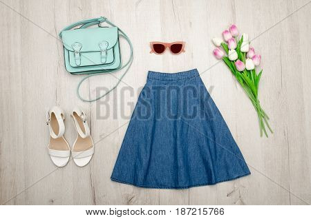 Jeans Skirt, Glasses, White Shoes, Handbag And A Bouquet Of Tulips. Fashionable Concept. Wooden Back