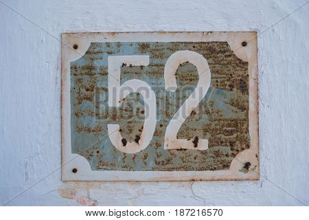 Very old rusty house number 52 plate on cracked white facade