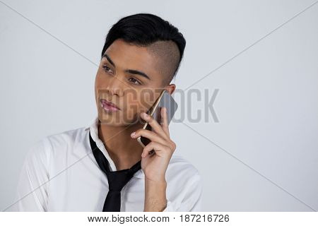 Transgender woman using smart phone while standing against white background