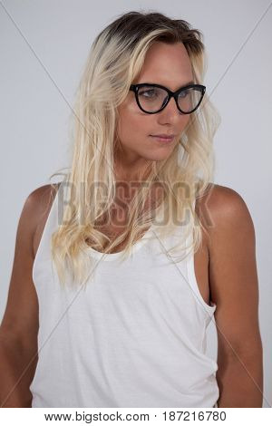 Transgender woman wearing eyeglasses standing against green background