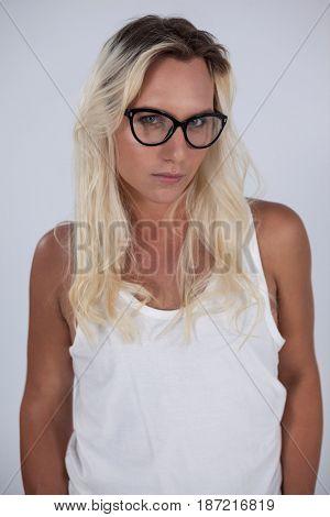 Beautiful transgender woman wearing eyeglasses standing over gray background