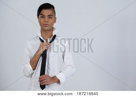 Portrait of transgender woman holding tie while standing against white background