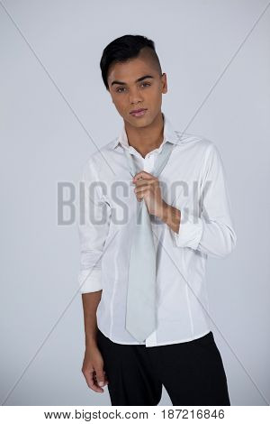 Portrait of transgender woman holding tie while standing against gray background