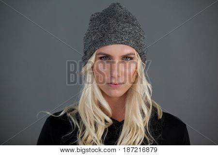 Portrait of transgender woman wearing knit hat gray background