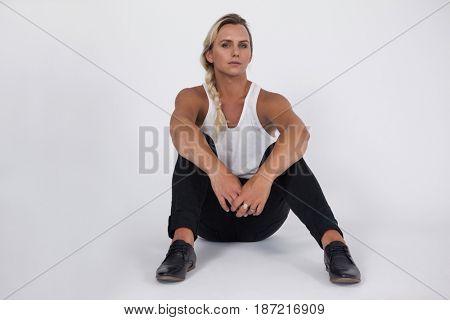 Portrait of transgender woman sitting over gray background