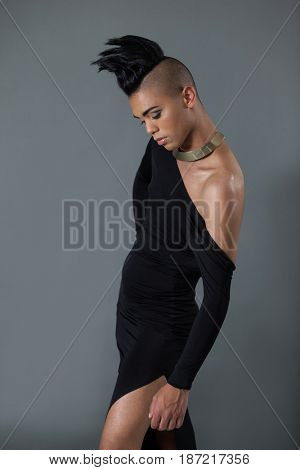 Transgender with half shaved hairstyle posing against gray background