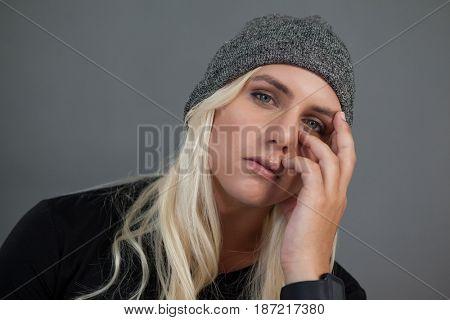 Portrait of transgender woman wearing knit hat against gray background