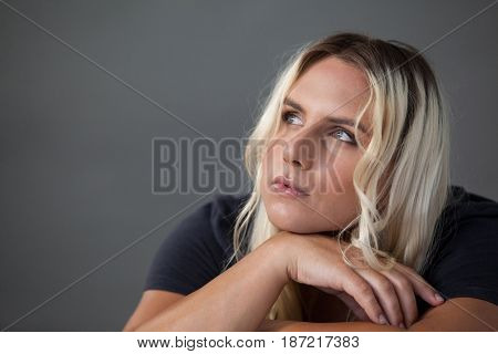 Thoughtful transgender woman leaning on chair over gray background