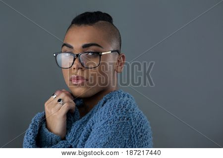 Portrait of transgender woman wearing eyeglasses against gray background