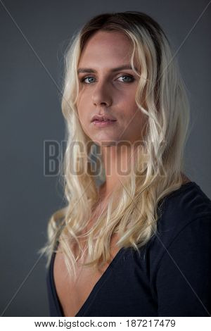 Portrait of beautiful transgender woman over gray background