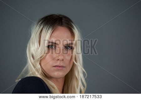 Portrait of transgender woman with blond hair gray background