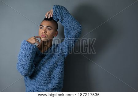 Confident transgender posing while standing over gray background