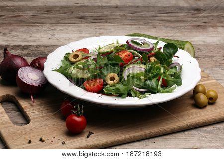 Caprese. Caprese salad. Italian salad. Mediterranean salad. Italian cuisine. Mediterranean cuisine. Tomato mozzarella basil leaves black olives and olive oil on wooden table. Recipe - Ingredients