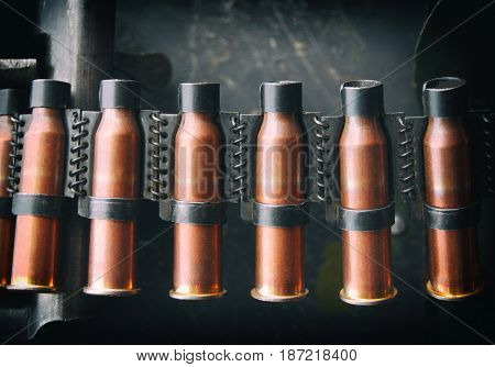 Copper-colored cartridges in the ammunition belts in the open air for a machine gun. Close-up