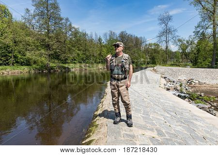 The fisherman walks along the dam on the Otava River. He is dressed in fishing clothes and goes fishing trout. River Otava South Bohemia Czech republic.