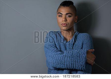 Portrait of confident transgender embracing against gray background